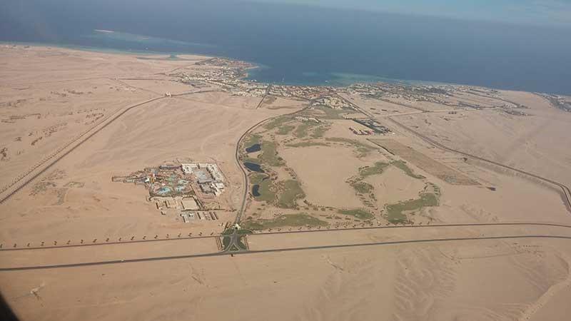 Flyfoto av Makadi  banen mitt i Ørkenen langs Rødehavets kystlinje.