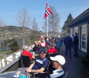 Spillere slapper av i sola på terrassen på Mandal Golfklubbs bane. (Foto: Tutti Ericson